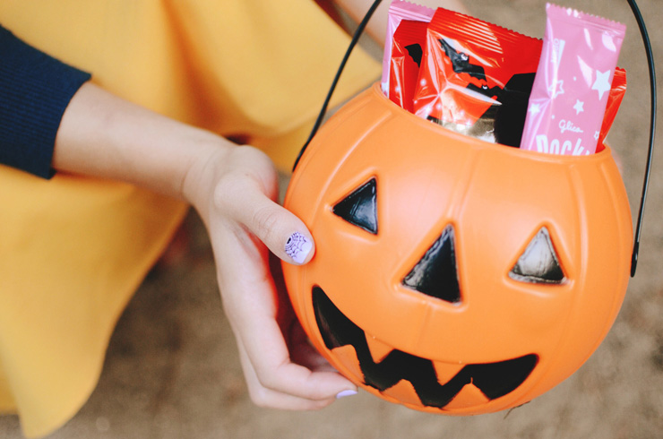 hanhgry.com | holding jack o lantern pail filled with candy