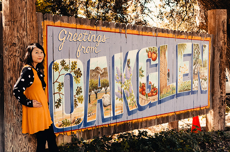 hanhgry.com | standing in front of greetings from oak glen sign