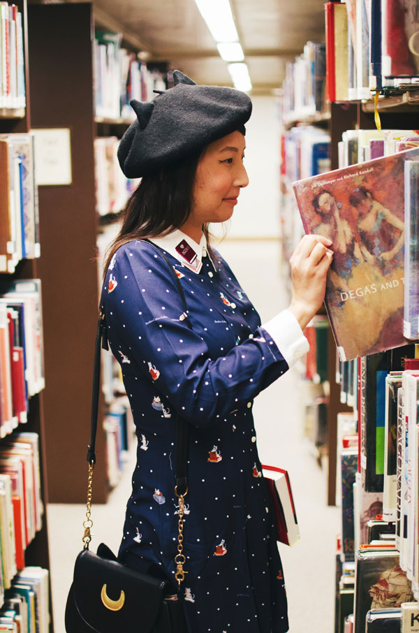 hanhgry.com | wearing a Miss Patina Kiterature dress with cat ear beret, pulling a Degas book off the shelf
