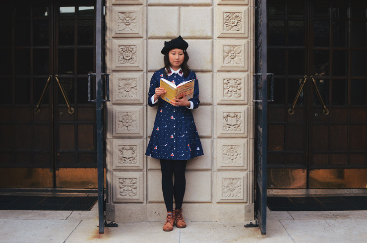 hanhgry.com | standing in front of library exterior holding a book, in Miss Patina Kiterature dress, looking down at book