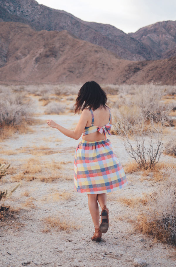 hanhgry.com | twirling in plaid dress, seen from the back, looking at camera in the anza borrego desert state park