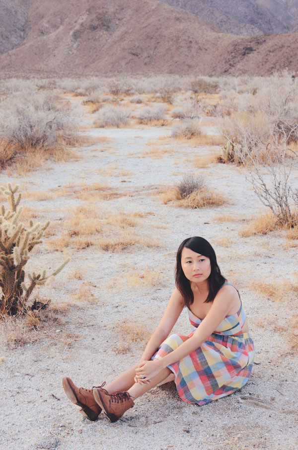 hanhgry.com | full body shot sitting in plaid dress, looking at camera in the anza borrego desert state park