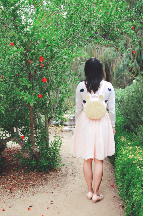 outfit: hanh standing in a gray polka dot GapKids sweater with a pink tulle skirt, shown from behind, wearing a rabbit shaped backpack made of straw