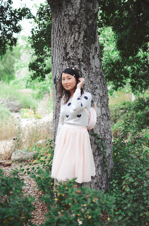 outfit: hanh standing in a gray polka dot GapKids sweater with a pink tulle skirt, surrounded by trees and bushes